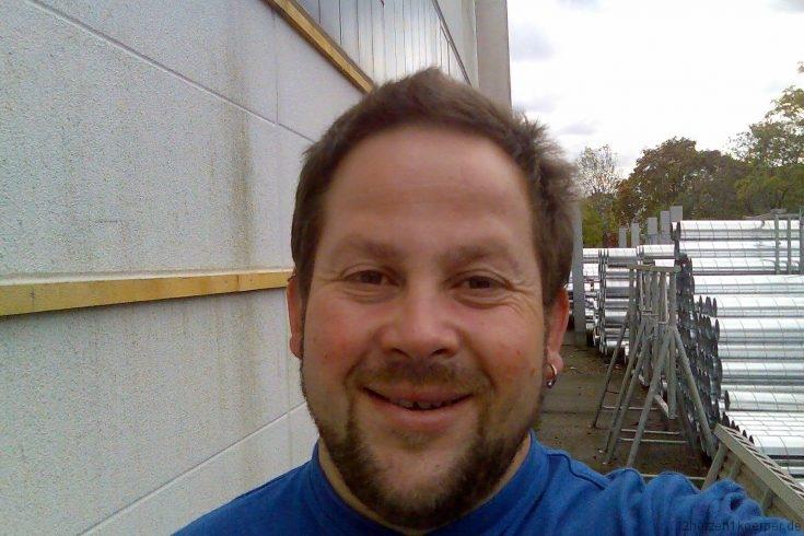 Peter, ca. 35 Jahre, lächelt fröhlich in die Kamera